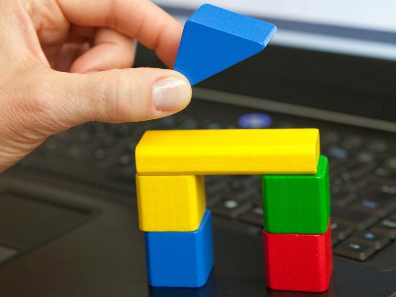 Bild zu Eine Hand legt Bausteine aufeinander