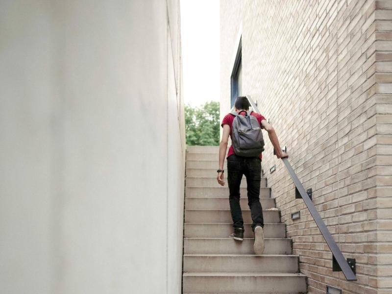 Bild zu Ein Flüchtling geht auf der Treppe nach oben