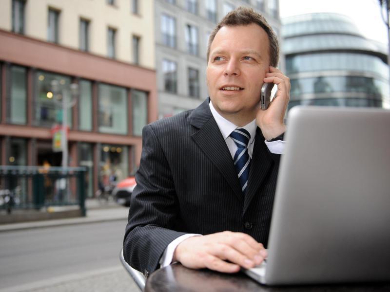 Bild zu Businessmann mit Laptop und Handy