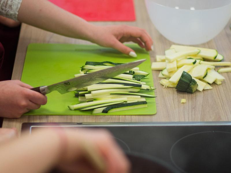 Bild zu Gemüse wird in einer Küche geschnitten.