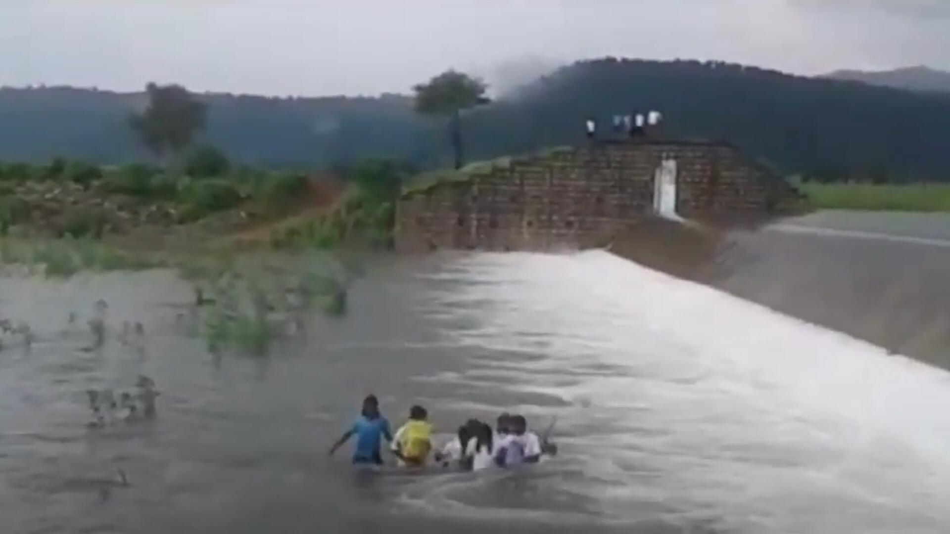 Bild zu Lebensgefährlicher Schulweg: Indische Schülerinnen waten durch reißenden Fluss