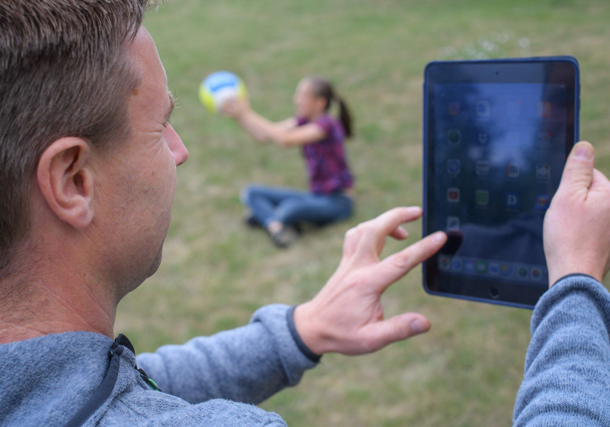 Bild zu Vater mit Tablet und Kind, das spielt