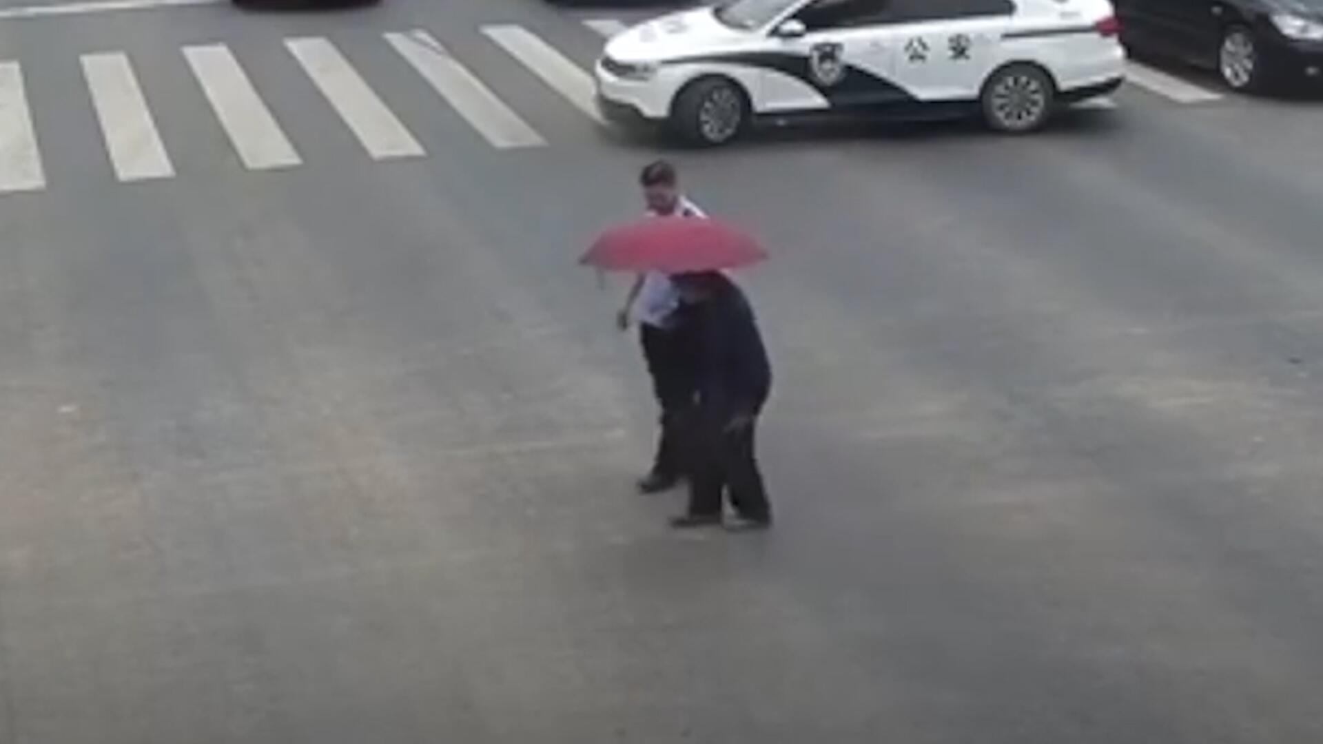 Bild zu China: Polizist stoppt Verkehr um alten Mann über die Straße zu begleiten
