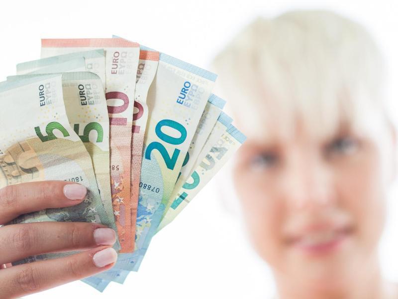 Bild zu Frau wedelt mit Geldscheinen
