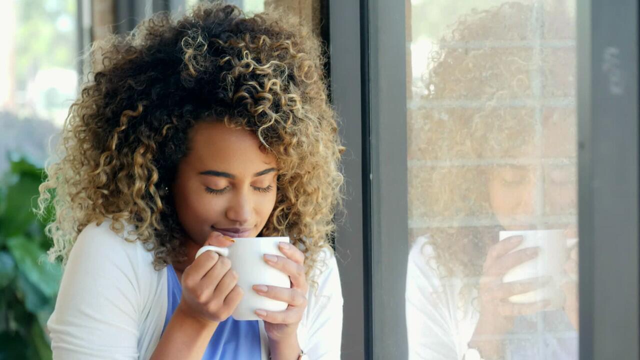 Bild zu Eine Frau trinkt heißen Ingwertee um ihre Halsschmerzen zu lindern.